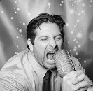 Image of man singing into microphone
