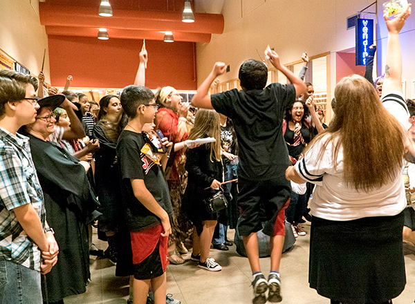 Teens cheering at a Harry Potter event.