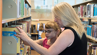 Mom with daughter browsing book shelves