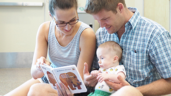 parents reading board book with baby